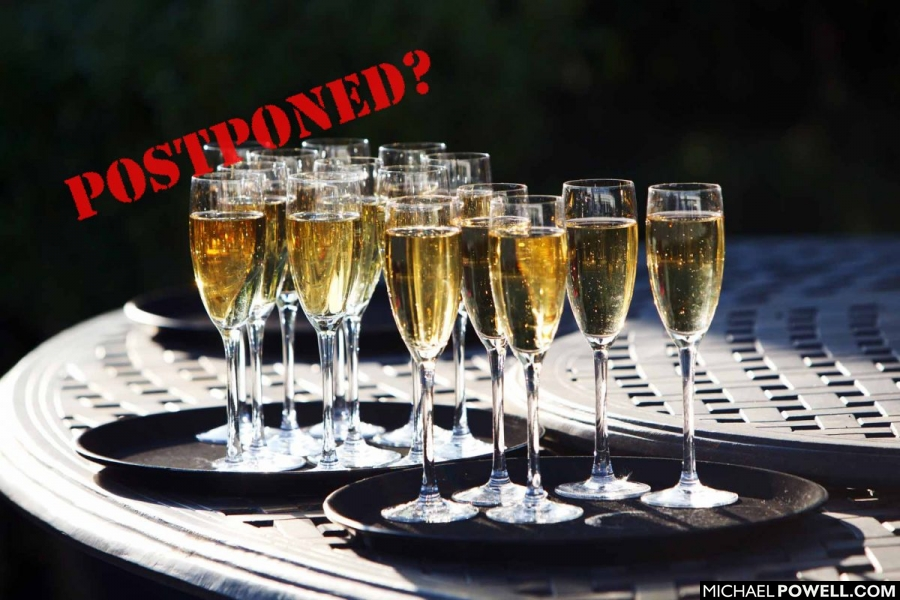 Pic shows champagne glasses overlaid with postponed rubber stamp text