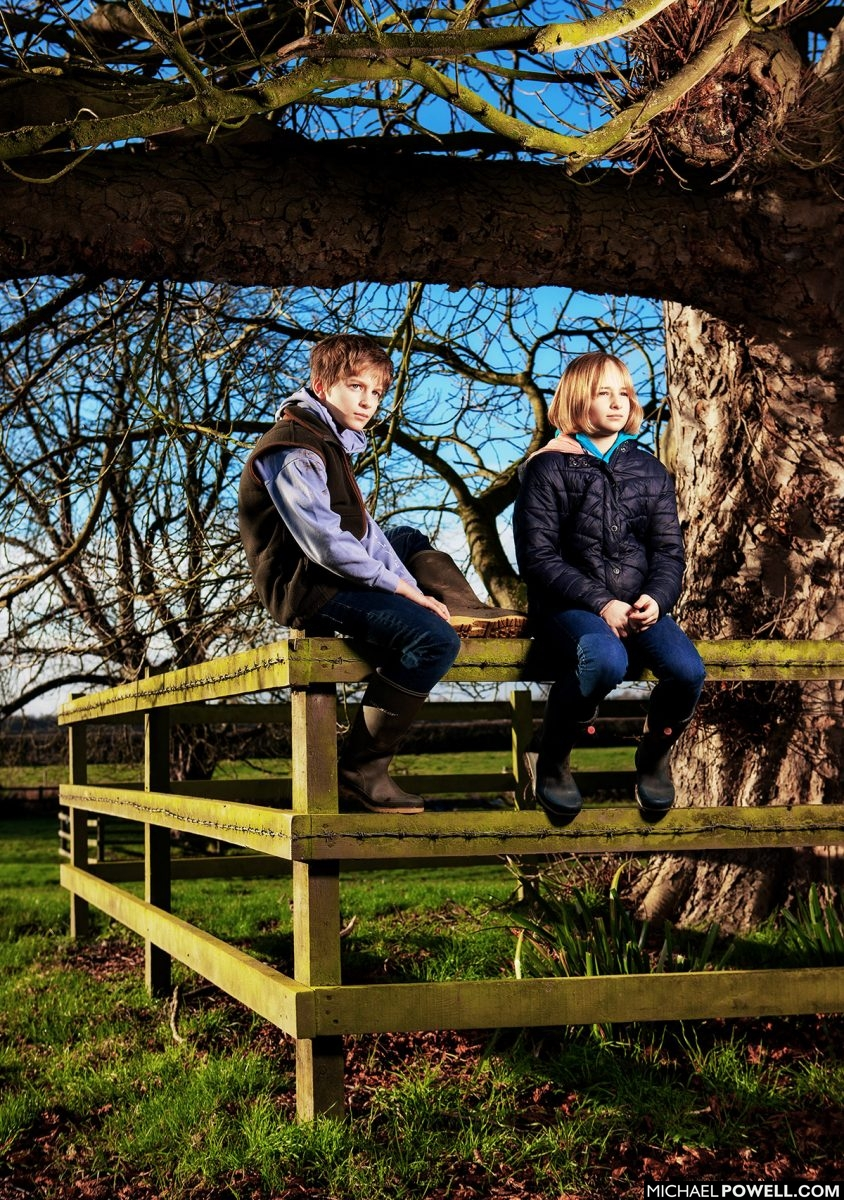 Lincolnshire family portraits of brother and sister sitting on fence in field.