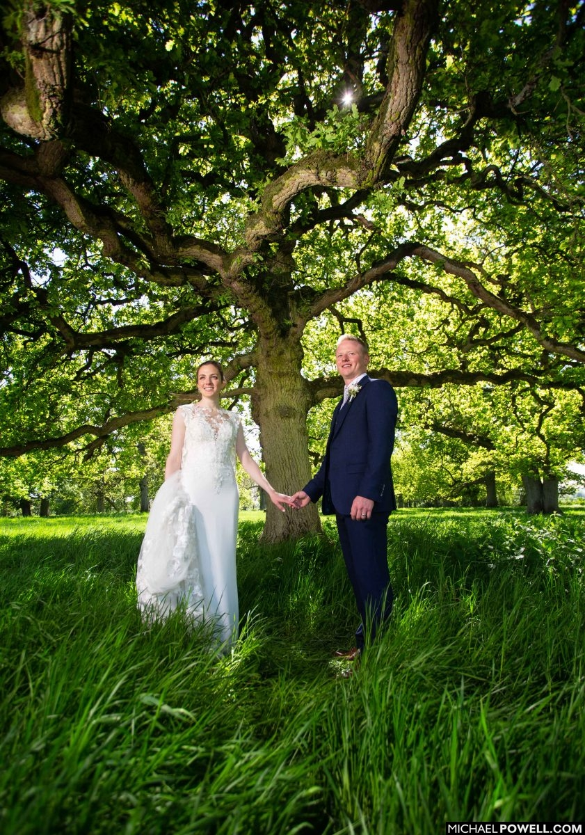 Newly married couple in Lincolnshire stand together in shade of a tree.